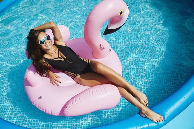 スタイリッシュな黒のビキニと魅力的なサングラスで完璧なセクシーなボディを持つファッショナブルな幸せと笑顔のブルネットモデルの女性は、屋外のスイミングプールで膨脹可能なピンクのフラミンゴでポーズ Premium写真