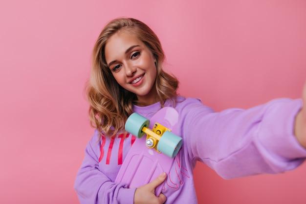 自分撮りを作るスケートボードでファッショナブルな幸せな女の子。バラ色で自分の写真を撮るのんきな巻き毛の女性。 無料写真