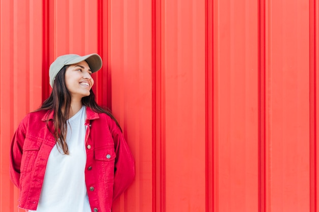 Fashionable happy woman looking away against red background Free Photo