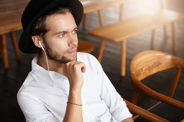 Giovane felice alla moda che indossa cappello nero e auricolari sognare ad occhi aperti, godendo il nuovo album musicale della sua band preferita online, utilizzando l'applicazione gratuita su dispositivo elettronico mentre ti rilassi al caffè Foto Gratuite