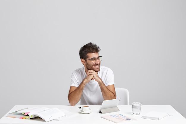 流行のヒップスターのひげを剃っていない学生がトレンディなヘアスタイルを職場に座っています 無料写真