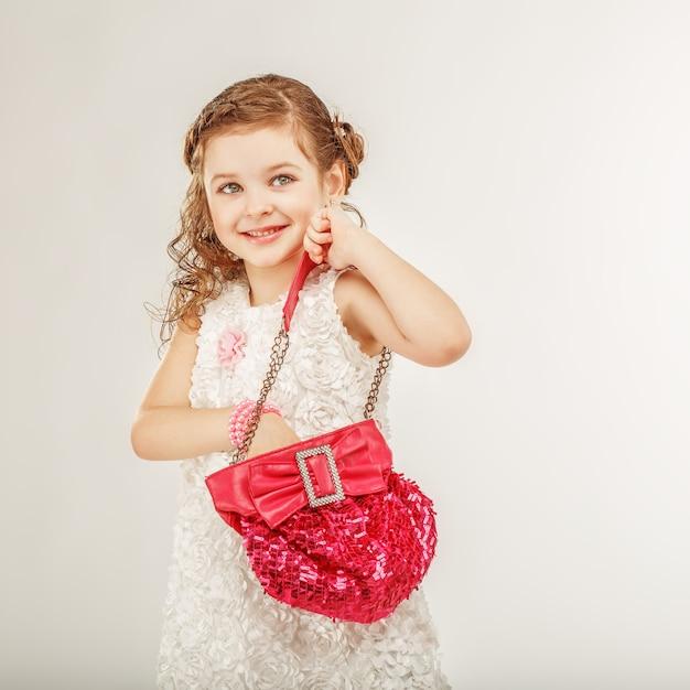Modna Mała Dziewczynka Trzyma Różową Torebkę Premium Zdjęcia