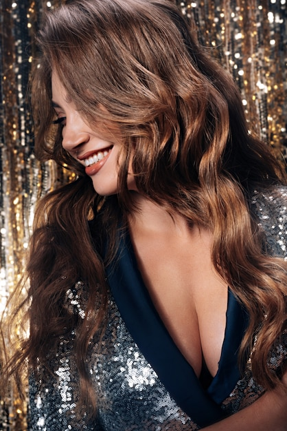 Fashionable and luxurious brunette in a motherboard with sequins and healthy strong hair came to the new year party Premium Photo