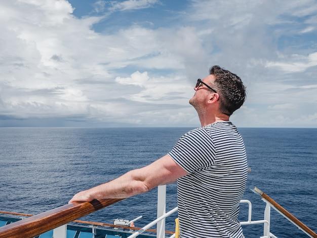 海の波を背景にクルーズ客船の空のデッキでファッショナブルな男。 Premium写真