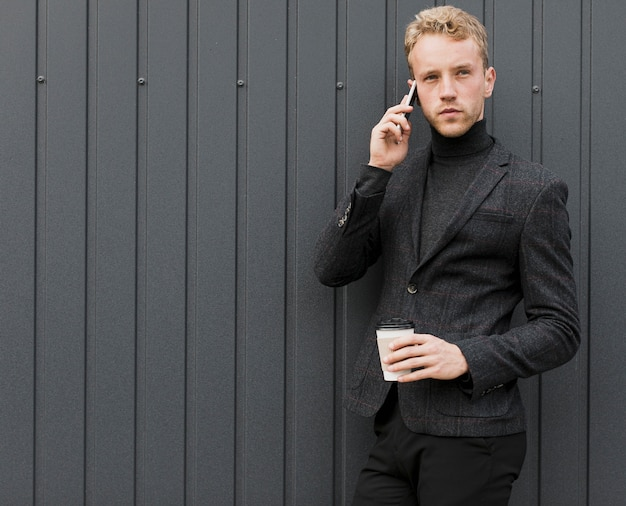 Fashionable man with coffee talking on the phone Free Photo