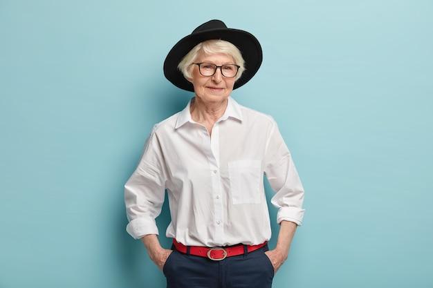 유행 성숙한 여인은 세련된 검은 모자, 흰색 셔츠와 빨간 벨트가 달린 바지를 입고 주머니에 손을 넣고 파란색 벽 위에 고립 된 기쁜 표정을 가지고 있습니다. 사람, 나이 및 패션 컨셉 무료 사진