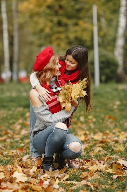 娘とファッショナブルな母。黄色い秋。赤いスカーフの女性。 無料写真