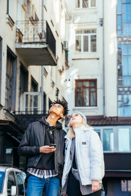 Fashionable multi ethnic couple looking up at building Free Photo