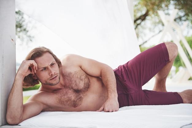 Модный сексуальный идеальный мужчина на пляже. Бесплатные Фотографии