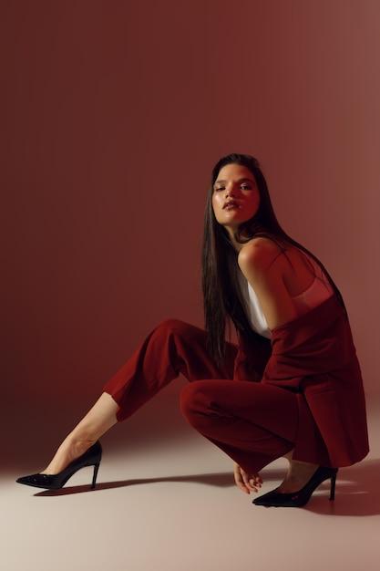 유행 앉아있는 여자 포즈, 컬러 스튜디오 조명, 세로 사진과 함께 세련된 사진. 고품질 사진 프리미엄 사진
