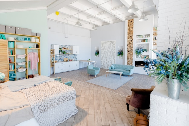 Fashionable spacious apartment with a stylish design in green, grey and white pastel colors with big window and decorative walls. bedroom and kitchen space Premium Photo