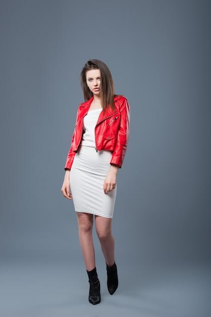 おしゃれなスタイル、ファッションの婦人服、色の組み合わせ。白いドレスと赤い革のジャケットの美しいブルネットの少女は灰色の背景を分離しました。 Premium写真