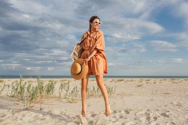 Fashionable summer image of beautiful brunette female in trendy linen dress , holding straw bag. pretty slim girl enjoying weekends near ocean.fell length. Free Photo