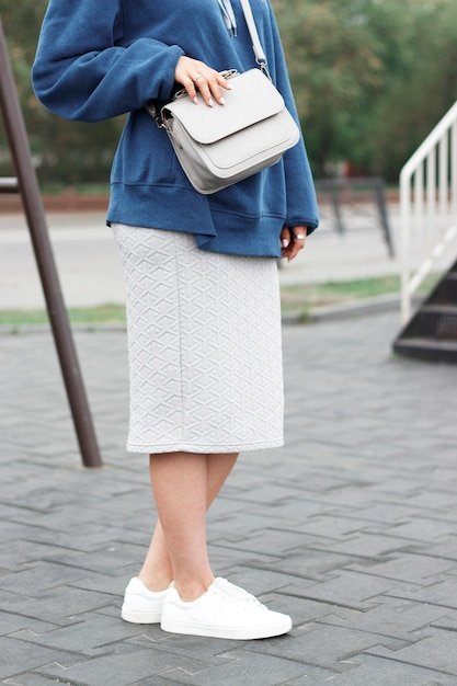 Fashionable summer outfit, a girl in a sweatshirt and white sneakers with bag Premium Photo