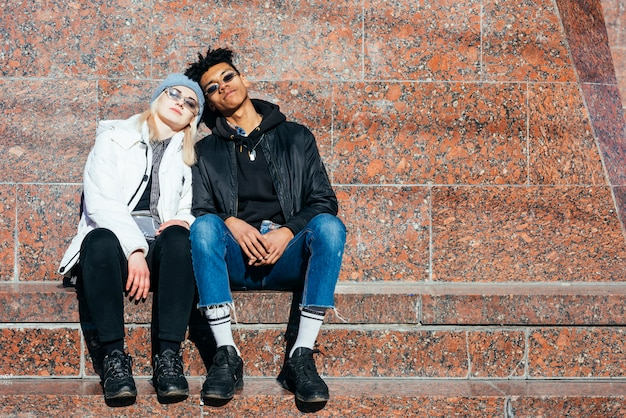 Fashionable teenage couple sitting together at outdoors Free Photo