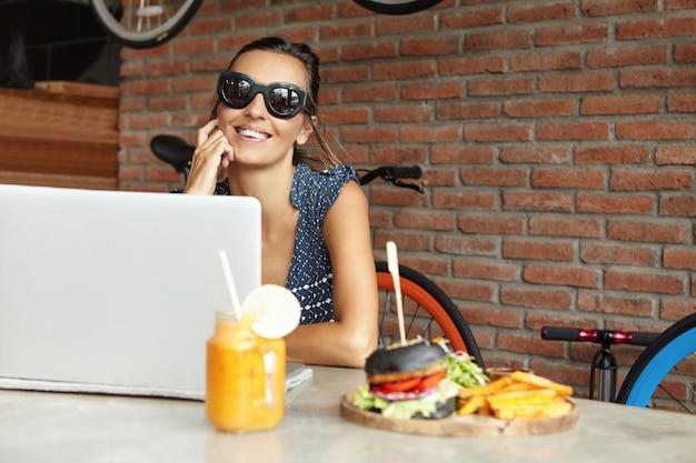 Модный видеоблогер в стильных солнцезащитных очках, записывающий видео с веб-камеры на портативном пк, сидя у стены из красного кирпича современного кафе. счастливая женщина с красивой улыбкой, серфинг в интернете на портативном компьютере Бесплатные Фотографии