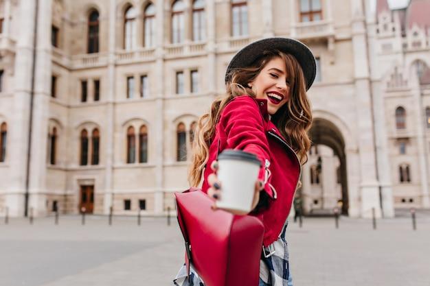 Donna bianca alla moda che posa con la tazza di latte sulla parete di architettura Foto Gratuite