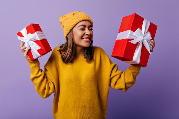 Модная белая женщина ждет рождества. портрет довольной девушки брюнет с красными подарками на новый год. Бесплатные Фотографии