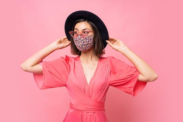 유행 여자 옷 보호 세련된 얼굴 마스크. 검은 모자와 선글라스를 쓰고. 분홍색 벽 위에 포즈 무료 사진