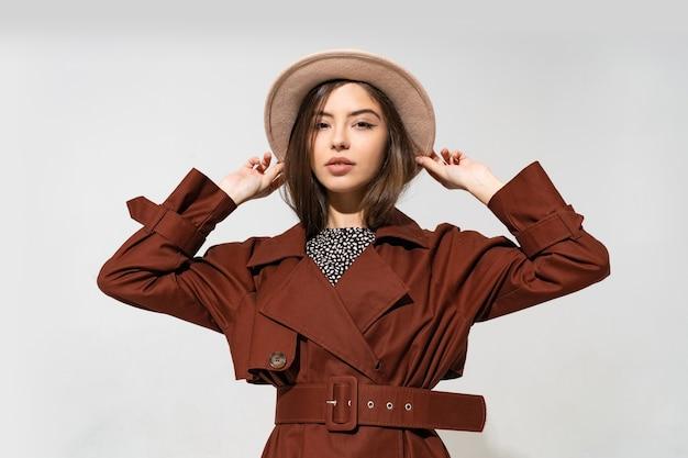 Модная женщина в коричневом пальто и бежевой шляпе позирует Бесплатные Фотографии