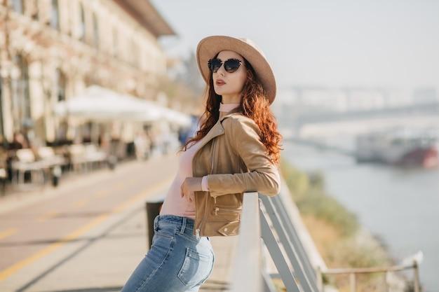 강 벽에 사진 촬영을 즐기는 캐주얼 청바지에 유행 여자 무료 사진