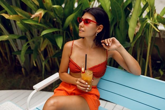 Модная женщина в ретро очки отдыха в тропическом пляжном клубе в стильный красный топ и оранжевые шорты. пить вкусный лимонад. Бесплатные Фотографии