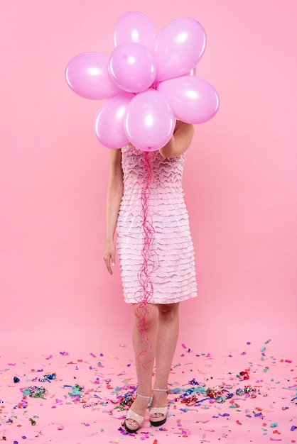 Fashionable woman at party holding balloons Free Photo
