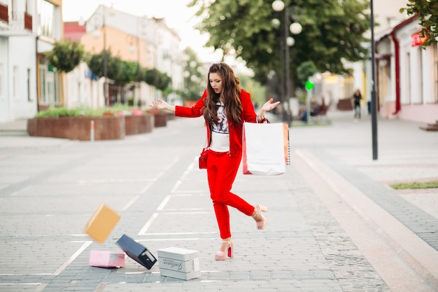 Fashionable woman in red suit with shopping bags dropped shoe boxes in the street. Premium Photo