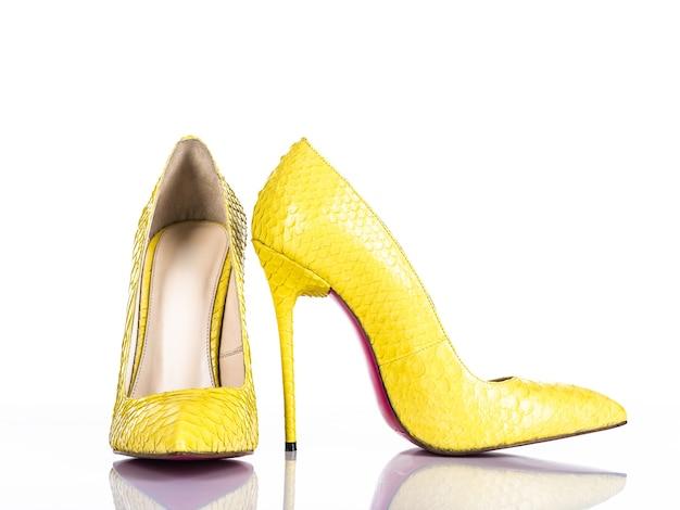 Scarpa tacco alto della donna alla moda isolata su priorità bassa bianca. bello pattino femminile giallo dei tacchi alti. lusso. Foto Gratuite