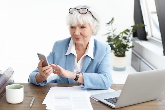 インターネットをサーフィンしたり、スマートフォンでテキストメッセージを入力したり、オフィスの机で働いたり、開いているラップトップの前に座ったりして、白髪と眼鏡をかけたファッショナブルな女性シニアアーキテクト 無料写真