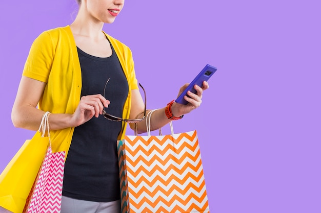 Fashionable woman using cellphone with holding colorful paper bag and eyeglasses Free Photo