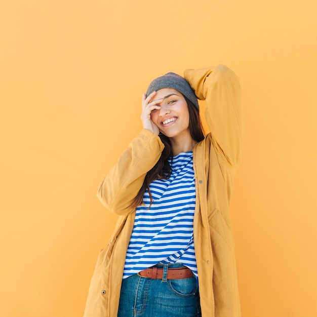 Fashionable woman wearing jacket on striped t-shirt posing while looking at camera Free Photo