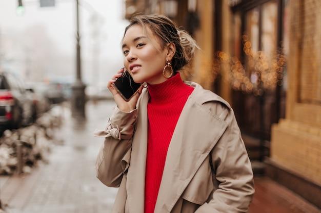 明るいトレンチコートと明るいセーターを着て素晴らしい気分で電話で話し、街を歩いているファッショナブルな女性 無料写真