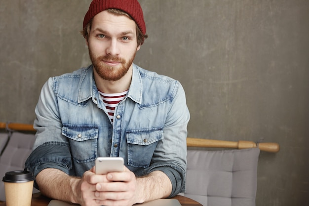 Модный молодой бородатый мужчина в шляпе и джинсовой рубашке сидит за столиком в кафе с бумажным стаканчиком свежего кофе, держит мобильный телефон во время обмена сообщениями в интернете и в интернете, используя бесплатный wi-fi Бесплатные Фотографии