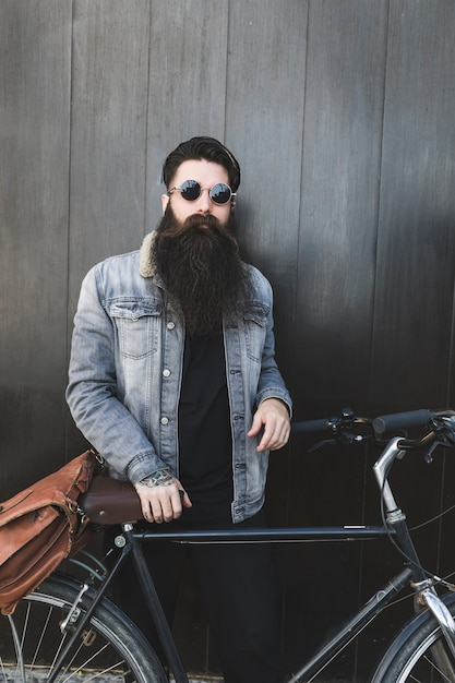 Fashionable young bearded man standing with bicycle in front of black wooden wall Free Photo