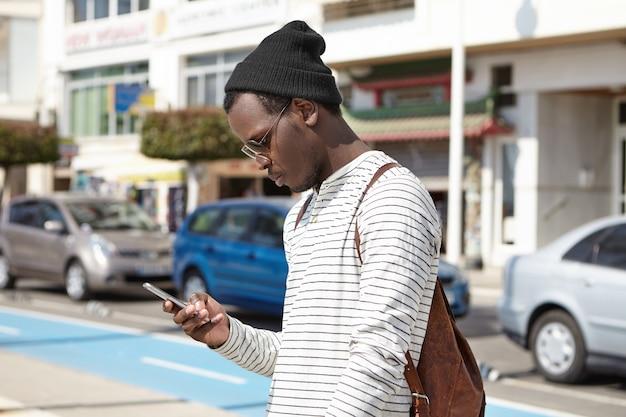 Модный молодой чернокожий турист с кожаным рюкзаком с серьезным выражением смотрит на смартфон в руках, используя приложение онлайн-навигации, ищет направление, пока теряется в большом городе Бесплатные Фотографии