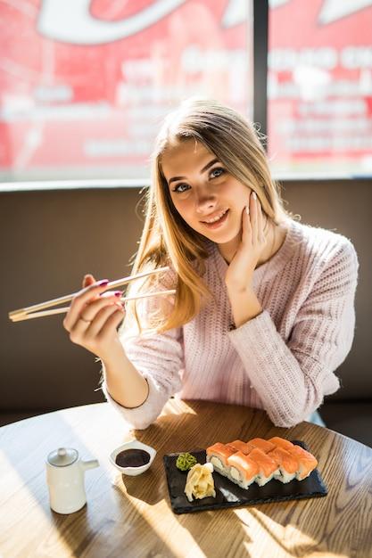 小さなカフェで昼食に寿司を食べる白いセーターでファッショナブルな若いブロンドの女性 無料写真