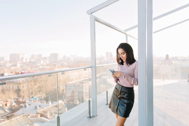 Fashionable young brunette woman in black skirt using phone on terrace on city view. Free Photo