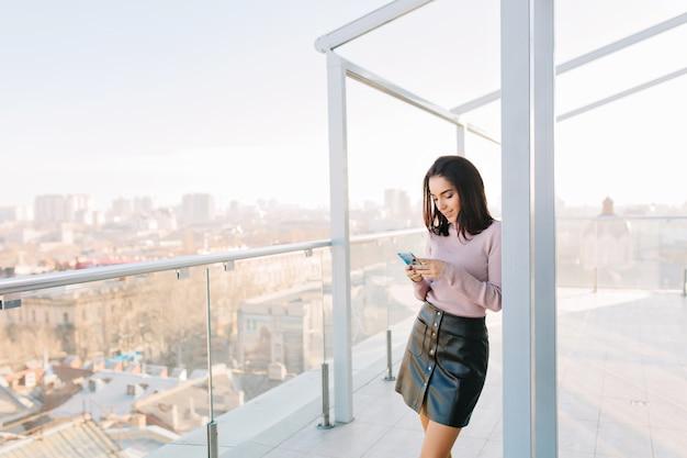 シティービューのテラスで電話を使用して黒いスカートのファッショナブルな若いブルネットの女性。 無料写真