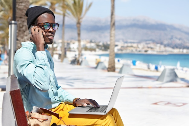 Fashionable young dark-skinned freelancer in hat and sunglasses having phone conversation on mobile while working remotely on laptop pc, sitting on bench in urban beach surroundings during holiday Free Photo