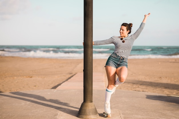 Fashionable young female skater holding pillar dancing at beach Free Photo