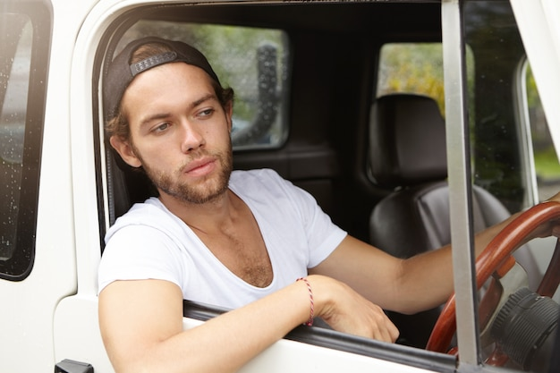 スナップバックを身に着けているファッショナブルな若い男が彼のスポーツユーティリティ車を運転し、彼の頭と肘を開いた窓から突き出して、心配そうな表情で道路を見て 無料写真