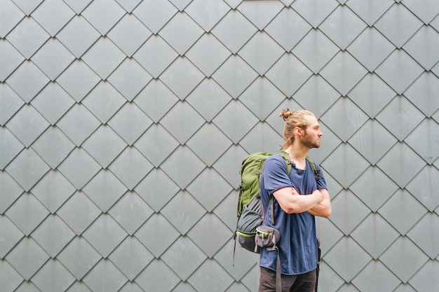 Fashionable young man with travel backpack looking away Free Photo