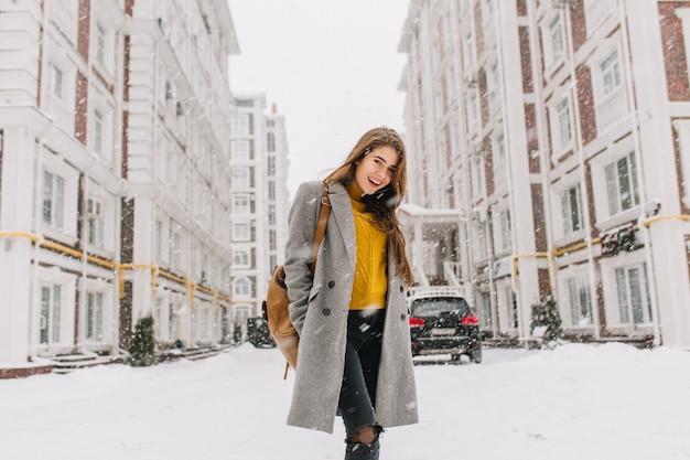 눈이 시간에 큰 도시에서 거리에 걷는 배낭 코트에서 유행 젊은 여자. 쾌활한 분위기, 강설량, 크리스마스를 기다리고, 긍정, 진정한 감정 표현. 무료 사진