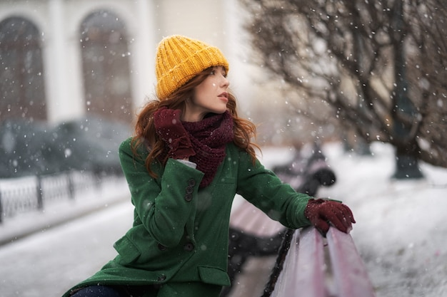 Fashionable young woman posing outside in a city street. winter portrait outdoors, in snowfall Premium Photo