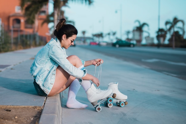 Fashionable young woman sitting on sidewalk tying the lace of roller skate on street Free Photo
