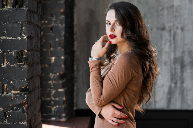 Fashionable young woman standing against wall Free Photo