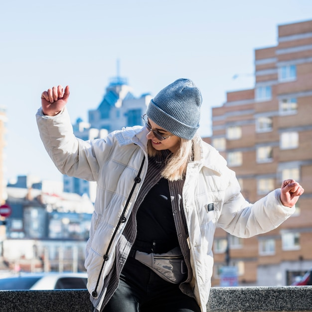 Fashionable young woman wearing blue knit hat dancing in the city Free Photo