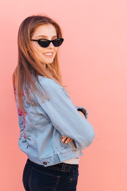 Fashionable young woman wearing sunglasses looking over shoulder against pink background Free Photo