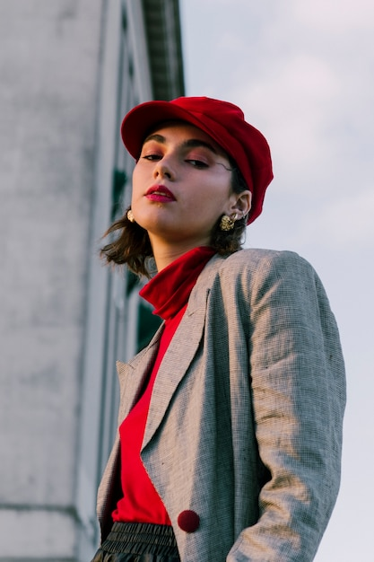 Fashionable young woman with red cap looking at camera Free Photo